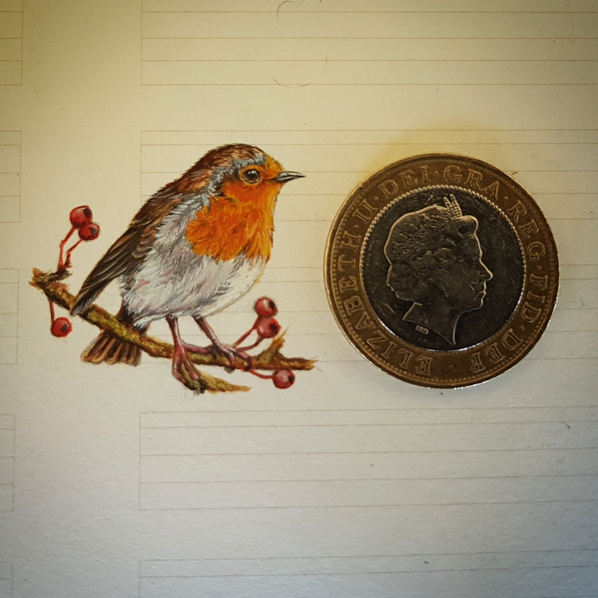 Miniature watercolour painting of robin with £2 coin for scale