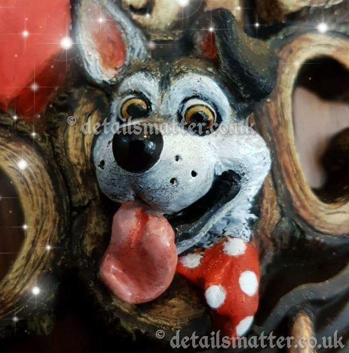 Cartoon grey/white malamute head wearing red an white spotted neck tie.